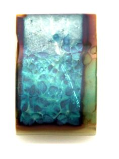This is French Vanilla glass with Silver Foil laid down then a sprinkling of Aquamarine frit spread over the bottom half. The French Valnilla Glass causes a reaction with the Silver Foil and the frit