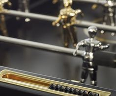 """This RS#3 Wood Gold Foosball Table offers a """"subtle and elegant combination of gold, metal, and wood."""" The players are plated with 24K gold. This foosball table is made from the finest materials and is as easy to play as any other premium (non gold) foosball table. The table comes with a score counter and goals that provide sleek angles and sight lines for onlooking fans. The arena appears to be suspended between the mighty player legs which feature 2 cross-beams and adjustable feet. Cross Beam, Sight Lines, Living Products, Gold Wood, Most Expensive, Angles, Beams, Counter, Play"""