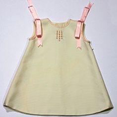 Vestido Claire de piqué en color beige con adornos en rosa. Sencillo y elegante. Bordado y confeccionado a mano.