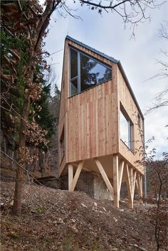 Wooden Cabin by A.LT ARCHITEKTI is raised on stilts over a hillside in Central Bohemia