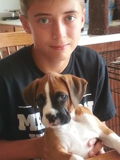 #PlowPets Michele's son with their 7-week-old boxer, Roxy.