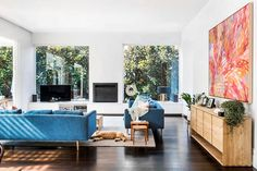 """*Magnolia grandiflora* 'Teddy Bear' trees fill the large picture windows, bringing colour and texture to the new living room. Jetmaster fire from [Agnews Fireplaces](http://www.agnews.com.au/