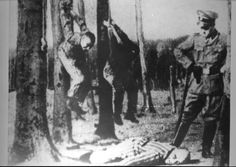 Buchenwald, Germany, Sommer, a SS guard, next to prisoners hanged by their hands. Hanged on the left tree: The author Karl Schnog (1897-1969), cabaret author and journalist who survived Dachau, Sachsenhausen and Buchenwald. Hanged on the right tree: Otto Feuer. The man lying face-down is Jack Werber