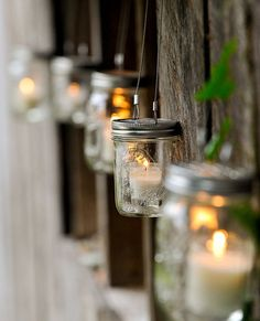 HANGING MASON JARS WITH GLASS VOTIVES AND LIT CANDLES LINE A WEATHERED PICKET FENCE.