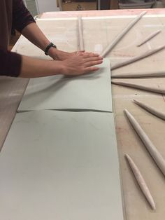 Cynthia smooth the clay over the forms to create the undulations of the porcelain mural tile at Natalie Blake Studios