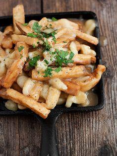 Canalizar Canadá con una montaña de papas fritas, cuajadas de queso y salsa.