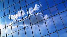 Low angle medium shot time lapse reflections of clouds rolling past glass office building