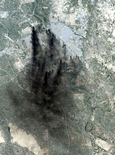 Fires from coalition bombing during the second war in Iraq provided a dramatic, smoke-filled satellite Landstat image over Baghdad. The Tigris River snakes north to south in this image. Baghdad International Airport is west of the smoke. April 2, 2003