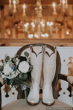 Stunning shot of white cowboy boots for bride on wedding day - shown in front of chandelier next to white and green bouquet {Heather Purvis Photography}