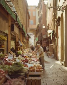 Narrow cobblestone streets with baskets of produce - the perfect grocery store.   |Bologna, Italy| |Source|