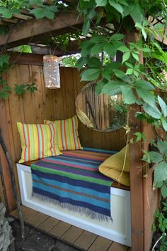 At the back of the garden, a shady hideaway seat for a cup of tea and a book. Inexpensive string lights in a shade adds coziness, and the oval bevelled-glass mirror adds depth and glitter.