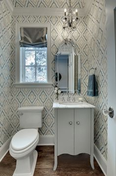 Chic, small powder room with blue and gray quatrefoil wallpaper and glossy white satin crown molding. Toilet sits below window covered in gray roman shade with Greek key ribbon trim. Crystal chandelier over gray washstand with marble countertop and Allen + Roth Hovan Arch Frameless Mirror. Chic gray scalloped bathroom vanity with white marble top and polished nickel faucet set.