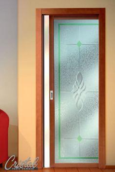 Porta scorrevole in vetro interno muro. Stipite e anta tanganica tinto ciliegio. Dettaglio esclusivo la lavorazione a mosaico con composizione di givrè bianco, antico verde chiaro e bevels trasparente.
