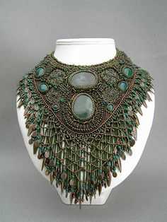 Necklace | Betty Stephan. 'Bronzed Beauty'. Agate cabochons and metal dangles and findings. Double fringe with netted bead work over hanging fringe.