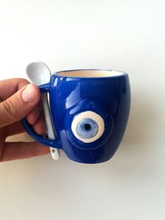 He encontrado este interesante anuncio de Etsy en https://www.etsy.com/es/listing/262460983/evil-eye-mug-with-spoon-coffee-mug-nazar