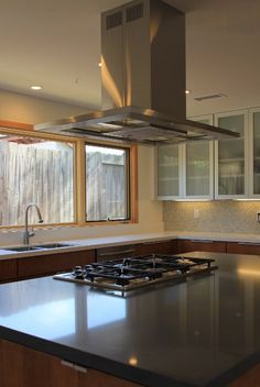 Modern kitchen; black counter contrasted with white counter, wood cabinets, kitchen island, counter top stove