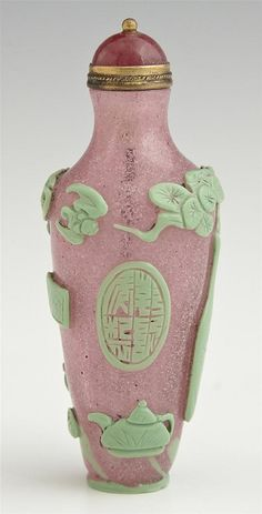 Pink Snowflake Peking Glass Footed Snuff Bottle, c. 1880, of tapered cylindrical form, with green glass overlay of flowers, a bat, a cloud, and scholar's items, with a Peking glass stopper, from the Christian collection