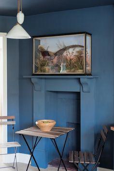 """Une cheminée bleue pour un coin au charme intemporel. """" Stiffkey Blue parvient à produire un effet à la fois théâtral et optimiste dans un espace sobrement décoré. Le côté spectaculaire découle de sa profondeur inégalée, inspirée par la vase et le sable d'une plage de la côte nord du Norfolk, tandis que la note de fraîcheur a été ajoutée par le blanc All White appliqué sur la plinthe et rappelé par l'abat-jour."""""""