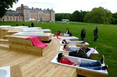 French studio Bruit Du Frigo provides a resting spot by installing wooden bathtubs 'Chamarande Les Bain' in the middle of the park in Chamarande. Some of the tubs are not filled with water, but with cushions so they can be used as deckchairs by those not wanting to bath in a public place.