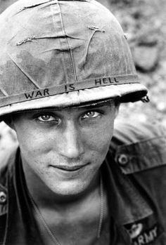 "An unidentified U.S. Army soldier wears a hand lettered ""War Is Hell"" slogan on his helmet, in Vietnam on June 18, 1965 – AP Photo/Horst Faas"