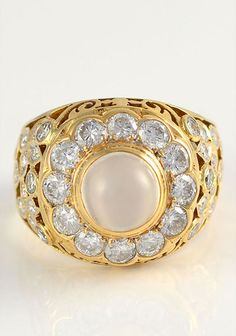Vintage 2.70 CTW diamond ring with moonstone. This 18 karat yellow gold ring has a round cats eye effect moonstone and 52 full cut diamonds at 2.70 carat total weight VS2-SI1 clarity G-I color, circa 1950. Size 9. Appraised at $7,500.
