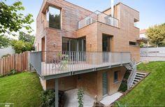 La Maison Bois présente à la fois une construction de qualité environnementale inspirée par la forêt voisine et la cascade en contrebas.