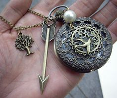 Hunger Games inspired necklace. It includes an arrow, a pearl, The Hanging Tree, clock, and Mockingjay. So cute!