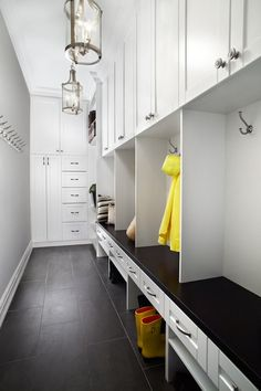 Vitali Design Build - laundry/mud rooms - long mudroom, mudroom, mudroom cabinets, mudroom lockers, open lockers, mudroom bench, staggered tiles, dark gray tiles, mudroom ideas, mudroom lanterns, wall of cabinets, floor to ceiling cabinets,