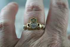 FABULOUS VINTAGE IRELAND, CELTIC CLADDAGH RING SHOW YOUR LOVE.....FREINDSHIP   FRIENDS AND LOVERS HAVE WORN THIS ROMANTIC IRISH JEWELLERY FOR OVER 300 YEARS. AN EMBRACE OF THE HANDS TO SIGNIFY FRIENDSHIP, HEART FOR ETERNAL LOVE, A CROWN FOR LOYALTY. GENUINE DIAMONDS AND NATURAL EMERALDS SET IN THE RING LOVELY CLAW SET 2 X EMERALDS TO THE CROWN 3 X BRILLIANT CUT DIAMONDS ON THE HEART AS WELL 2 X DIAMONDS EITHER SIDE OF THE SHANK GREAT COLLECTABLE AB=ND SORT AFTER STYLE TODAY STAMPED INSID...