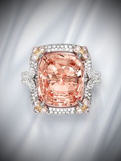 Platinum, 18 karat rose gold, padparadscha sapphire and diamond ring. In this feminine design, a cushion-cut papadparadscha sapphire weighing 10.27 carats is set at the corners with small round diamonds of pink hue, and its openwork mounting is further set with round near colorless diamonds.