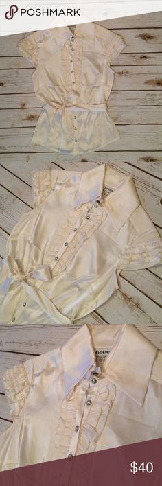 NEW Bebe Cream Stretch Silk Buttoned Blouse This NEW Bebe cream colored stretch silk blouse has crystal buttons and ruffle details on the cap sleeves and down along the buttons. It is very flattering on, with darts at the bust and panels to fit your curves. It would look great with a satin skirt, leather pants, or with your favorite fitted jeans! bebe Tops Blouses