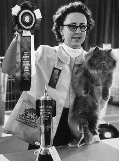 Best cat in show, blue female longhair called Bentveld Rosemary, is held by Judge Rotter. Owner is Mrs. Howell Mueller of San Antonio, Texas.