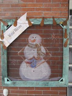 Snowman painted on the screen of a old window.