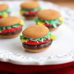 Mini Burger Cookies: Ingredients:  20 vanilla wafer cookies; 10 grasshopper fudge cookies OR York peppermint patties; 1 cup shredded coconut; green food coloring; 1 (4.25 ounce) Betty Crocker red decorator frosting; 1 (4.25 ounce) Betty Crocker yellow decorator frosting.