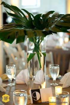 Monstera leaves for centerpieces, light brown table linens, white napkins