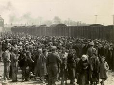 SS men divide newly arrived Jews by sex on the platform at Birkenau.  The smoke in the background is from crematoria working under extra-heavy demands.