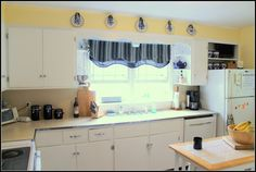 Image result for white kitchen cabinets and yellow walls with blue decor
