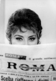 Actress Sophia Loren impishly peering over the top of Roma newspaper. LIFE, 1961