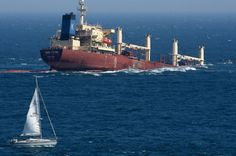 A sailboat passes by the sinking Panamanian cargo ship New Flame, which collided with an oil tanker Sunday in the Strait of Gibraltar, near Algeciras, ...