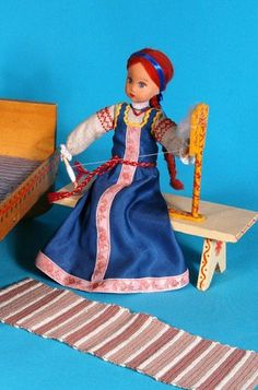 Doll in Russian costume spinning wool.
