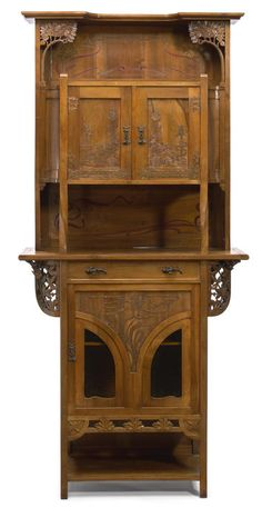 An Austrian Art Nouveau pewter inlaid and copper overlaid carved walnut and glass two part cabinet circa 1900.