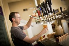 bartender pouring beer at Superior Bathhouse Brewery