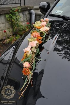 Striking floral wedding car decoration with green cymbidium orchids, sunflowers, roses, carnations and chrysanthemums in tones of pink and burnt orange. By abkwiaty.pl |