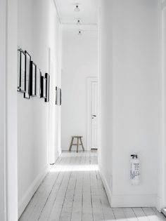 a corridor with white wooden floor.