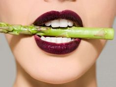 Woman in asparagus in her mouth - Getty Images/Image Source
