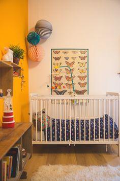 affiche vintage classe papillon plus un mur orangé donne un bel ensemble à cette chambre.