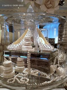 Wedding Dessert Table Decoration - Custom white cocoa butter painted molded Valrhona Opalys 33% white chocolate shoes with shiny silver sole and dragée studs. With vanilla bean macarons under HUGE glass cake dome to prevent snatching while on wedding display!