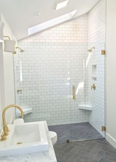 Master bathroom remodel with herringbone floors, white subway tile, brass fixtures, and floating wood vanity with marble top by Beebout Design.