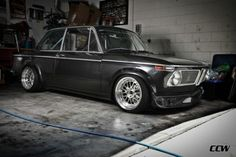 lowered BMW 2002 with modern rims & tires, roll cage