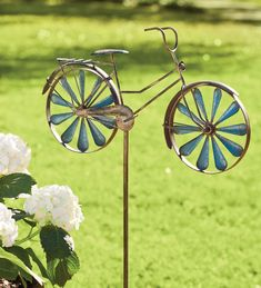 Nostalgic bicycle garden accent has spinning wheel inserts that take you for a spin back in time.